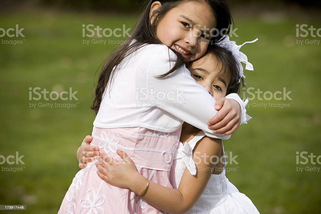 Asian Girls Hugging Each Other at Park in Easter Dresses stock photo