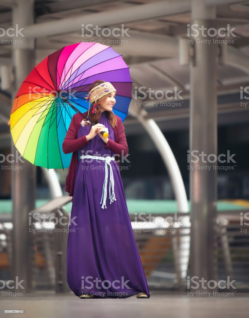 Asian girls standing and smiling in purple dress holding colorful umbrellas after rain. stock photo