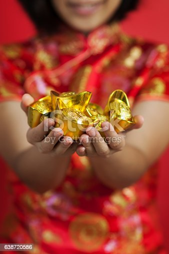 Chinese new year. Asian glasses woman with cheongsam holding gold Ingots on red background. Girl is smiling.