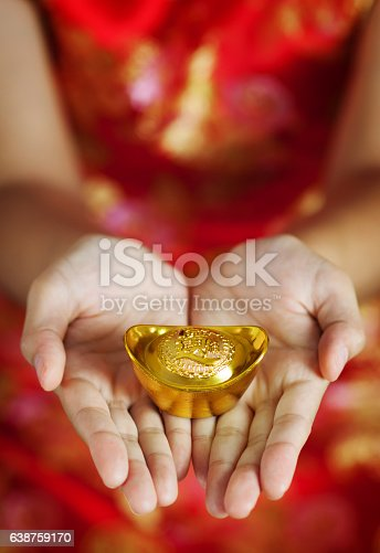 Chinese new year. Asian glasses woman with cheongsam holding gold Ingots on red background.
