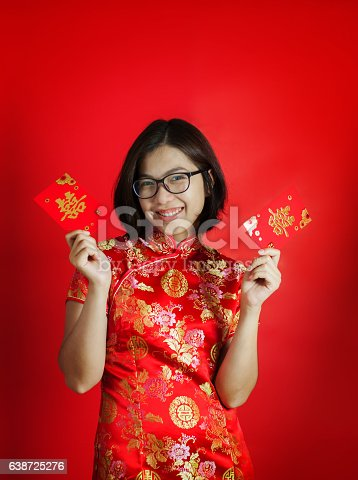 Chinese new year. Asian glasses woman with cheongsam holding red envelopes on red background. Girl is smiling.