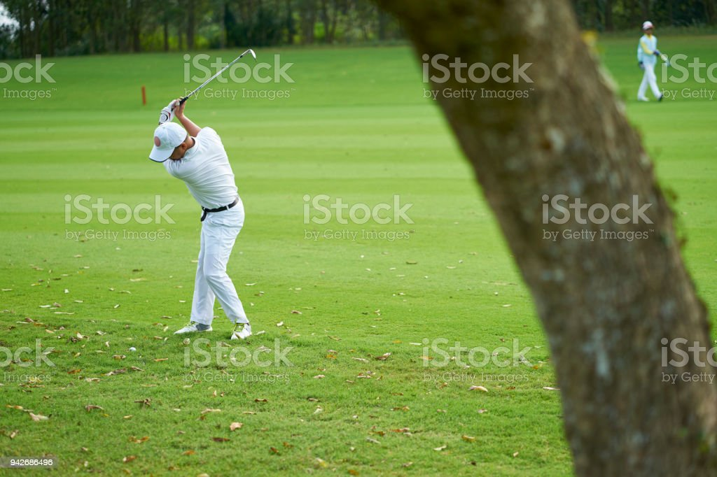 Asian golfer swinging club outdoors in course in summer stock photo