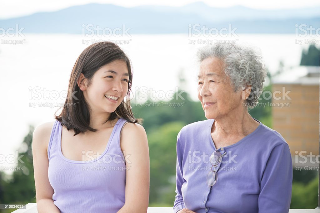 Asian Granddaughter and Senior Woman Enjoying View from Balcony, Canada stock photo