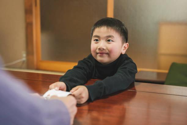 おとじ玉を手渡すアジアの祖父、新年に贈り物として与えられたお金を孫に - お年玉 ストックフォトと画像