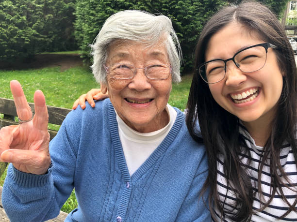 Asian Grandmother and Eurasian Granddaughter Smiling for Photo on Bench stock photo