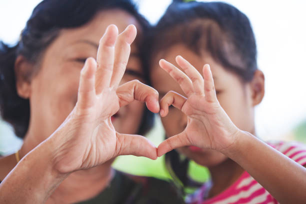 asian grandmother and little child girl making heart shape with hands together with love - optimistic zdjęcia i obrazy z banku zdjęć