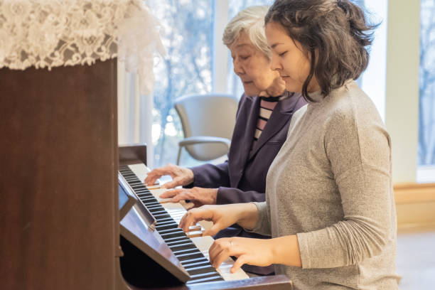 asian grandmother and mixed-ethnic granddaughter playing piano duet together - two students together asian foto e immagini stock