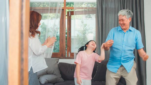 Asiatische Großeltern und Enkelin hören zu Hause Gemeinsam Musik und tanzen. Senior Chinese, Opa und Oma glücklich verbringen Familie Zeit entspannen mit jungen Mädchen im Wohnzimmer Konzept. – Foto