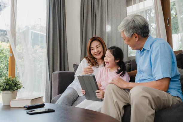 Asiatische Großeltern und Enkelin mit Tablet zu Hause. Senior Chinese, Opa und Oma glücklich verbringen Familie Zeit entspannen mit jungen Mädchen überprüfen Social Media, liegen auf dem Sofa im Wohnzimmer Konzept – Foto