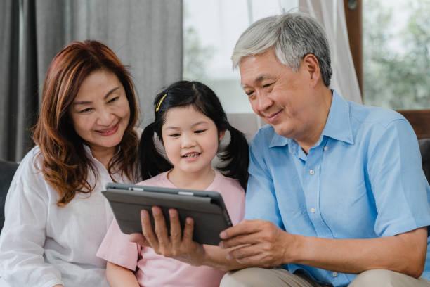 Asiatische Großeltern und Enkelin Videoanruf zu Hause. Senior Chinesisch, Opa und Oma glücklich mit Mädchen mit Handy-Video-Anruf im Gespräch mit Papa und Mama im Wohnzimmer zu Hause liegen. – Foto