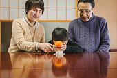 丸い餅にマンダリンオレンジを置くアジアの祖父母と孫