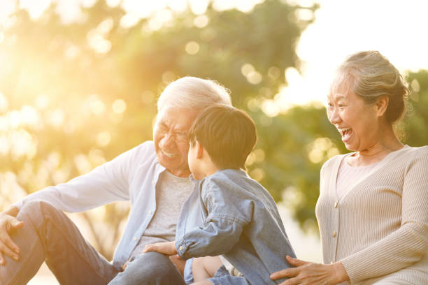 asian grandparents having fun with grandson stock photo