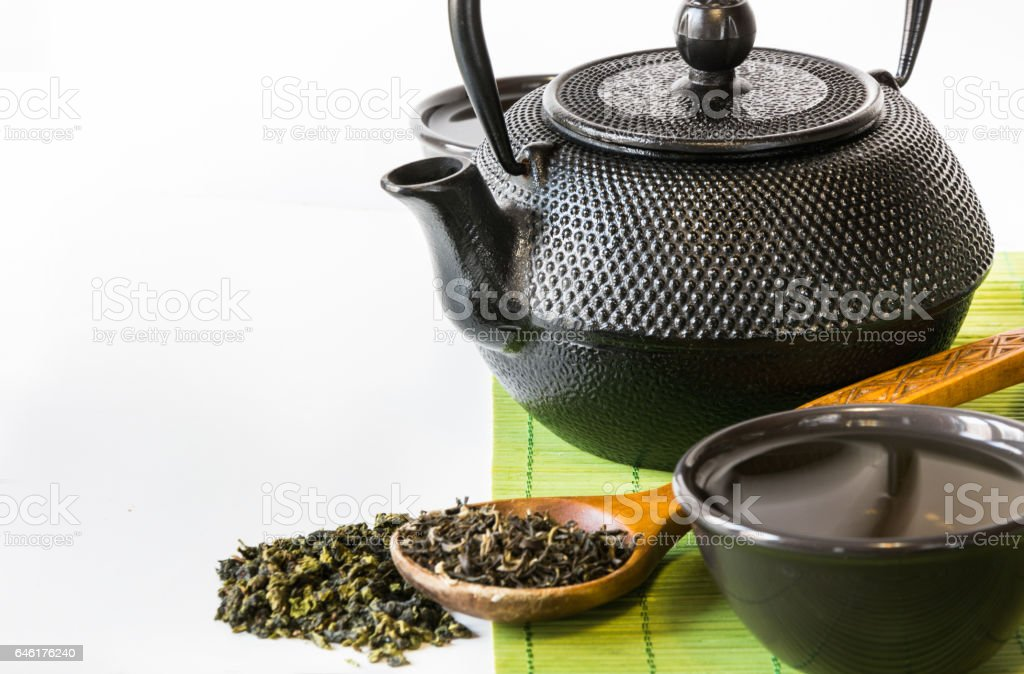 Asian green tea set on bamboo mat with dried green tea in spoon with copy space. Asian tea concept. stock photo