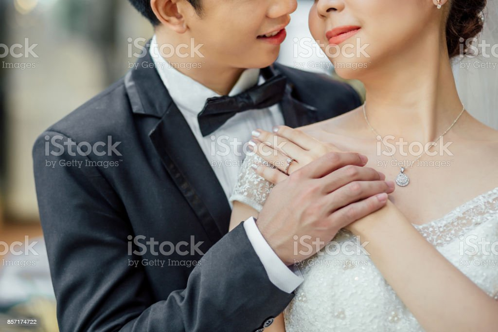Asian groom and Asian bride are close together and are about to kiss each other with a smiling and happy face.They hold hands together. stock photo