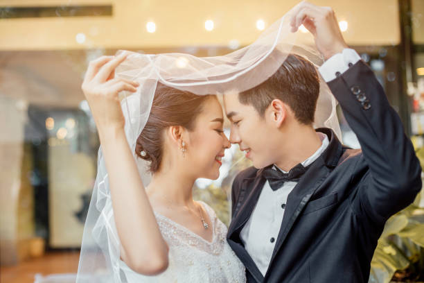 Asian groom and Asian bride are under viel together and are about to kiss each other with a smiling and happy face. stock photo