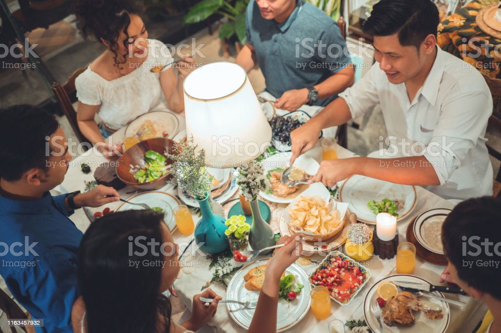 Asian group  friends eating dinner at home, they are happy to talk. Asian group  friends eating dinner at home, they are happy to talk. Adult Stock Photo