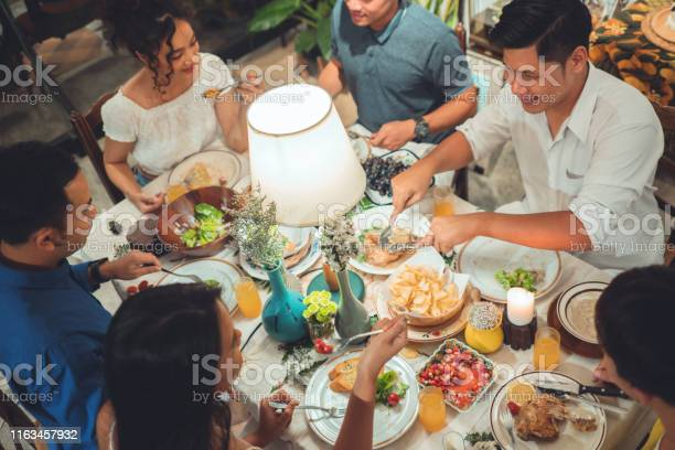 Asian Group Friends Eating Dinner At Home They Are Happy To Talk Stock Photo - Download Image Now