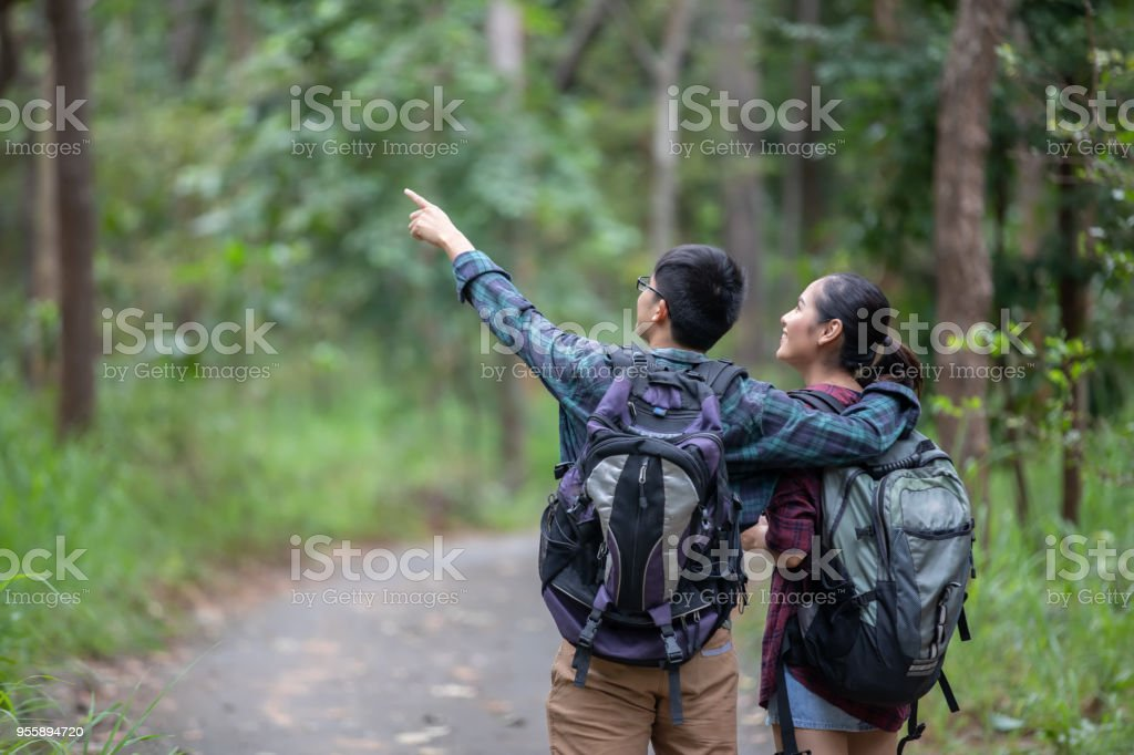 59298da590 Asian Group of young people Hiking with friends backpacks walking together  and looking map and taking photo camera by the road and looking happy