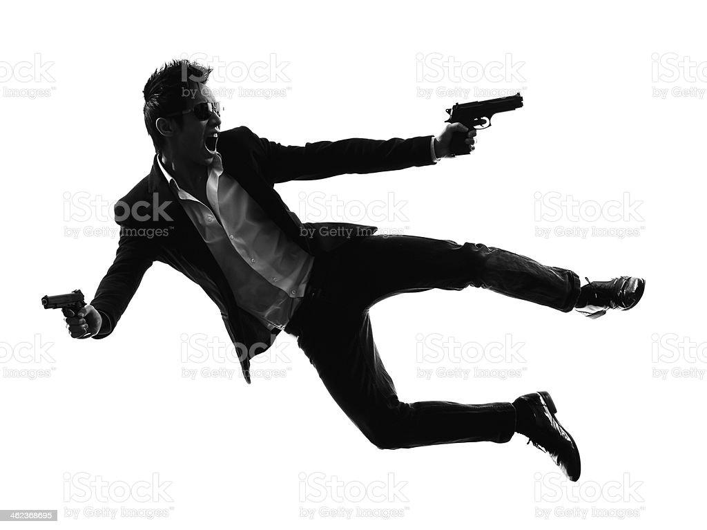 asian gunman killer jumping shooting silhouette stock photo
