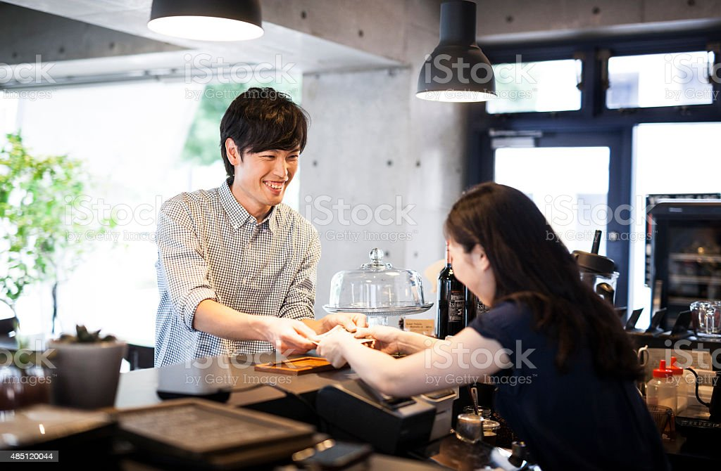 Asian guy paying in a cafe stock photo