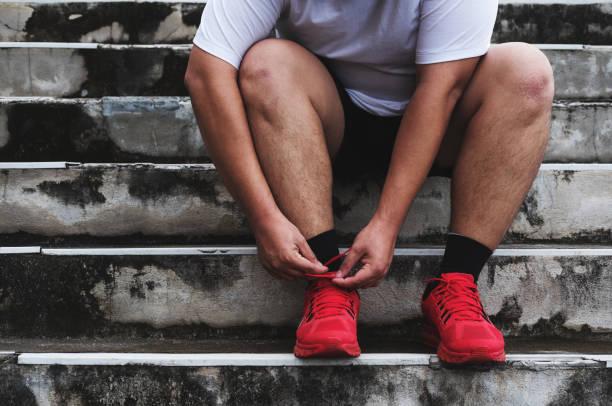asiaten binden laufschuh, vorbereitung zum laufen zum abnehmen - neue sneaker stock-fotos und bilder