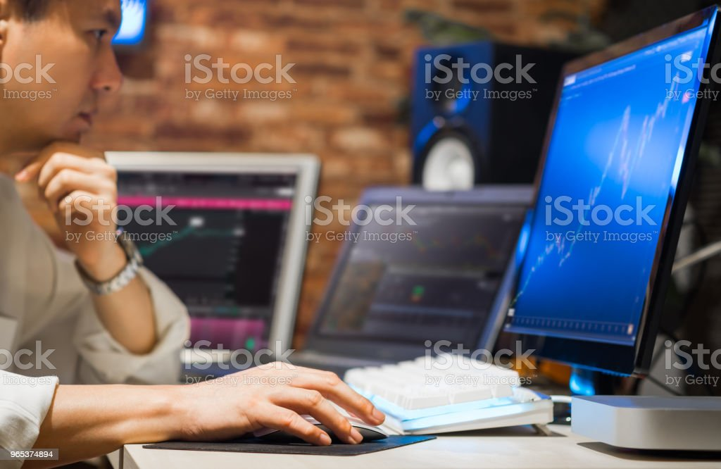 asian handsome business man working on multiple computer zbiór zdjęć royalty-free