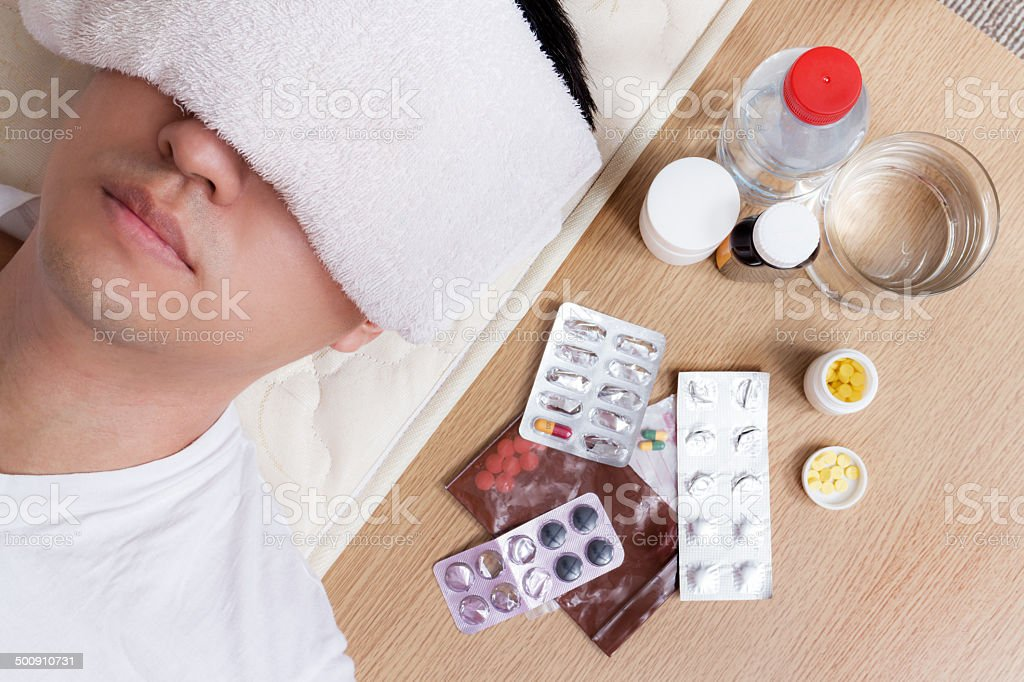 Asian Handsome Man in bed with tablets and water stock photo