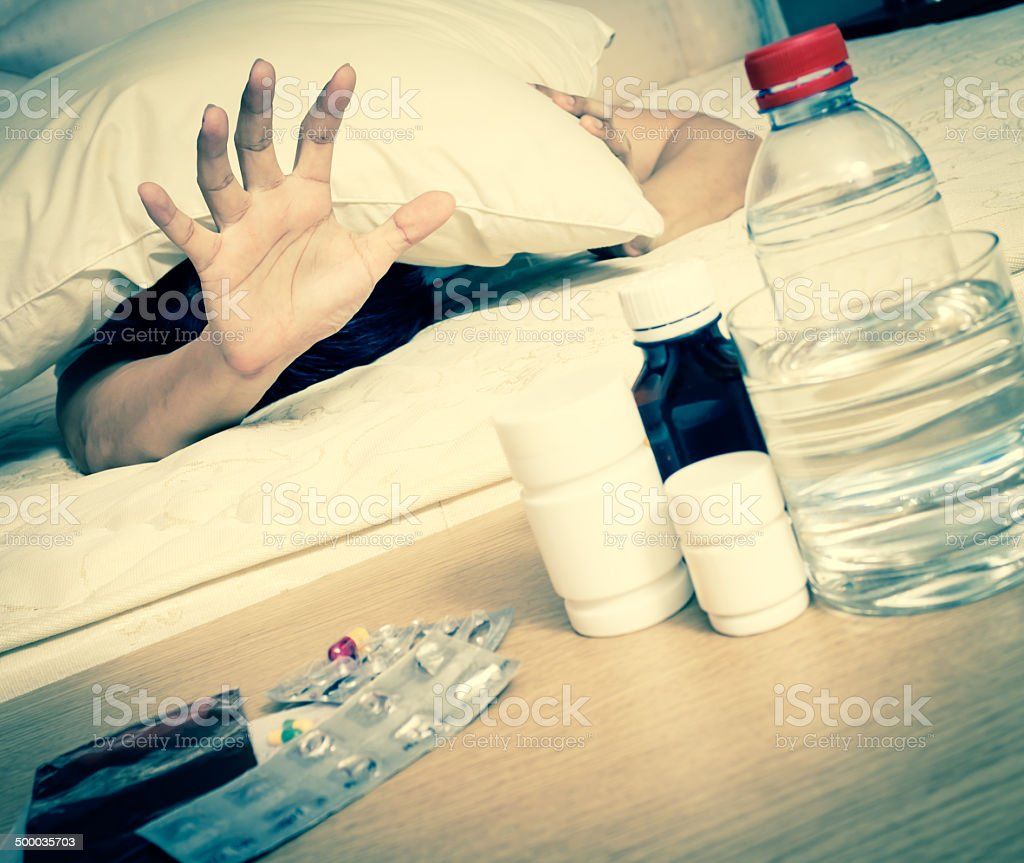 Asian Handsome Man in bed with tablets stock photo