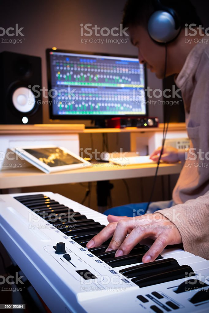 asian handsome musician composing song in recording studio stock photo