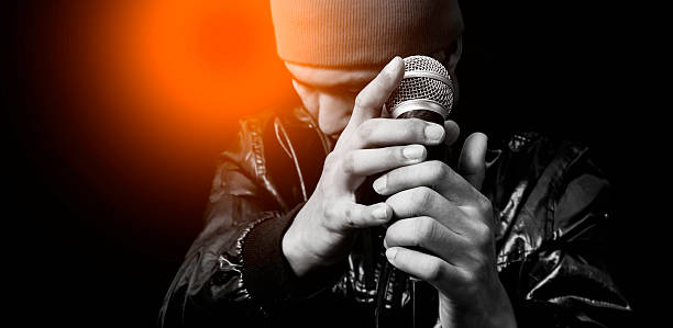 asian handsome singer posing on dynamic microphone asian handsome singer posing on dynamic microphone. focus on hand, isolated on black singer stock pictures, royalty-free photos & images