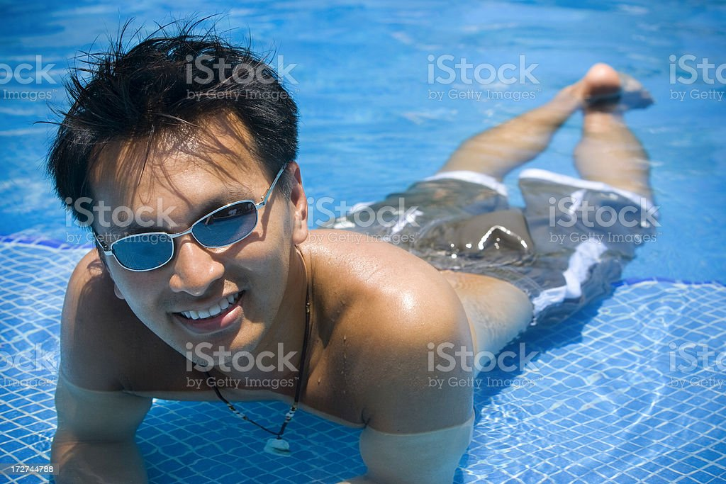 Asian Handsome Young Man Floating in Sunny Pool, Sunglasses, Copyspace royalty-free stock photo