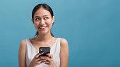 アジアの幸せな美しい女性ブロガーは、笑顔で、コピースペースで青い色の背景に隔離されたスマートフォンを保持しています。オンライン技術マーケティングのコンセプト。