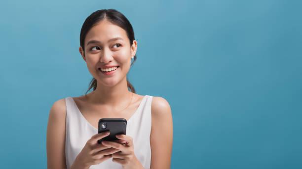 亞洲快樂美麗的女性博客微笑,拿著智慧手機隔離在藍色背景與複製空間。在線技術行銷的概念。 - 亞洲 個照片及圖片檔