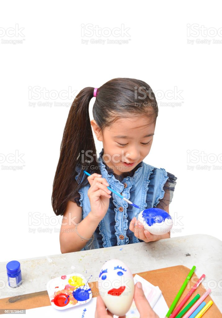 Asian happy girl with smile painting blue color on white egg for Easter day isolated on white background stock photo
