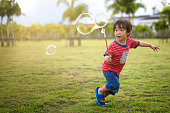 Asian Happy little kid blowing and playing soap of bubble wand in garden