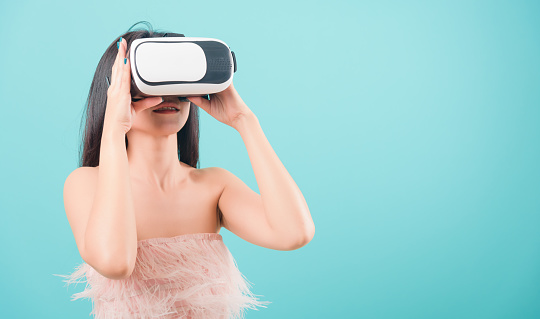 istock Asian happy portrait beautiful young woman standing smile her using a virtual reality headset, playing on VR glasses device 1212499146