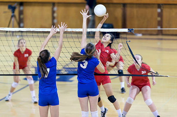 asian high school volleyball player spikes volleyball against female opponents - volleyball sport stock photos and pictures