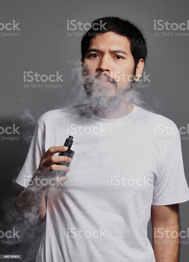 Asian Hipster man smoking electronic cigarette on grey background stock photo