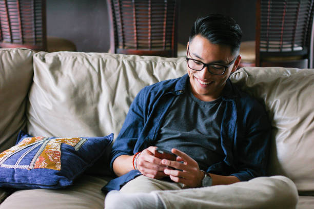 Asian hipster teen reading message stock photo