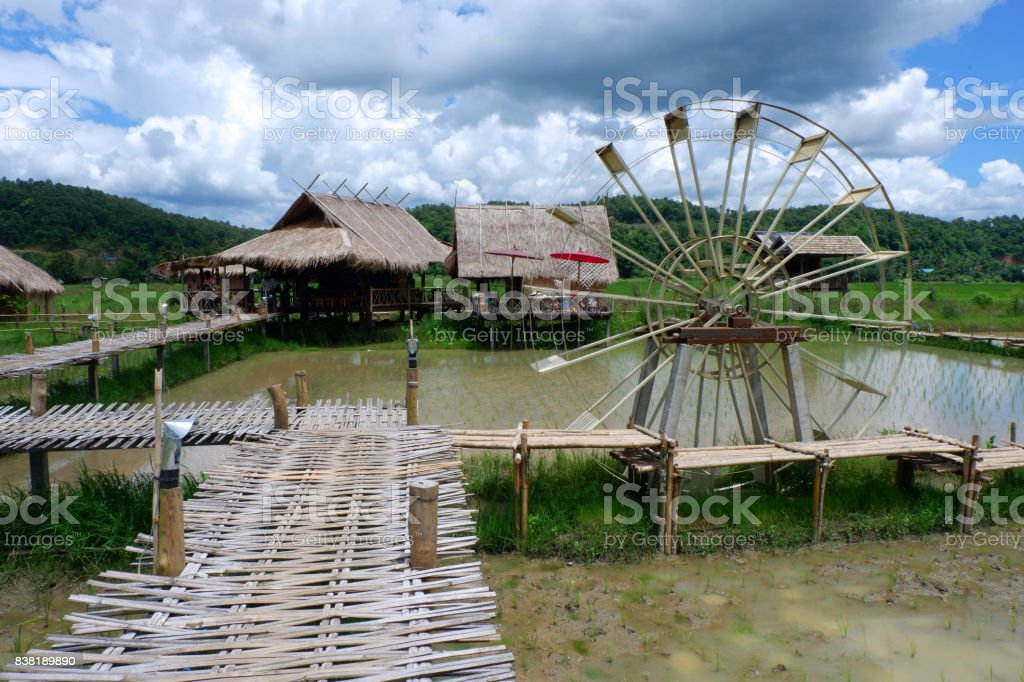 Asian house and water wheel in Southeast Asia. stock photo