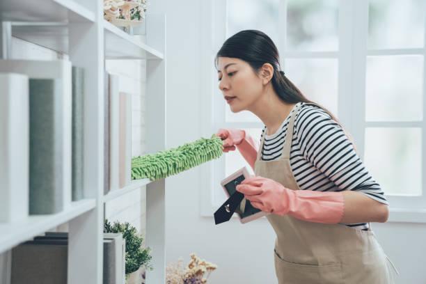 asian housekeeper in apron dusting the bookshelf stock photo