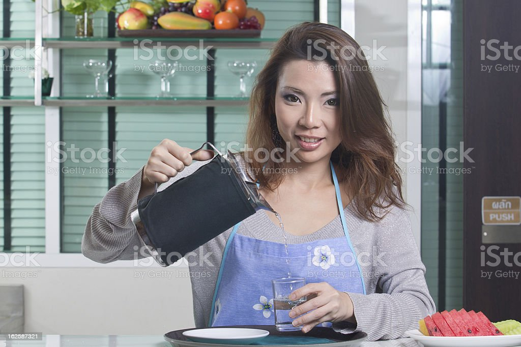 Asian housewife pouring water royalty-free stock photo