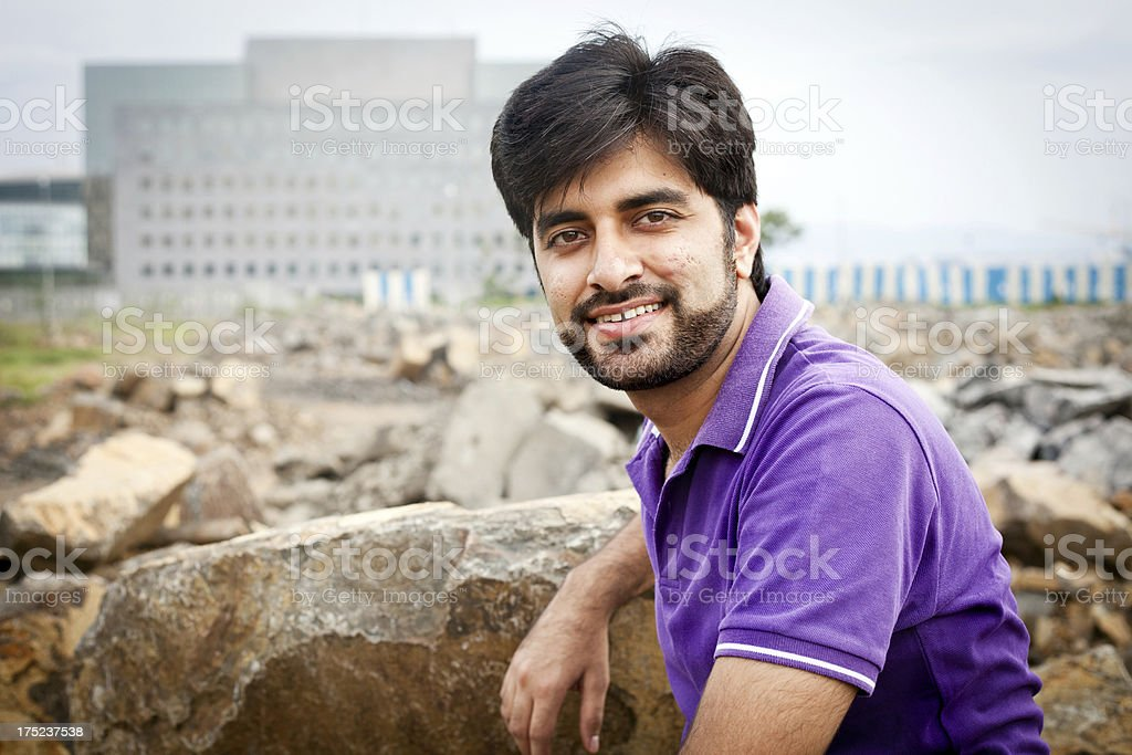 Asian Indian Attractive Young Man sitting Outdoors stock photo