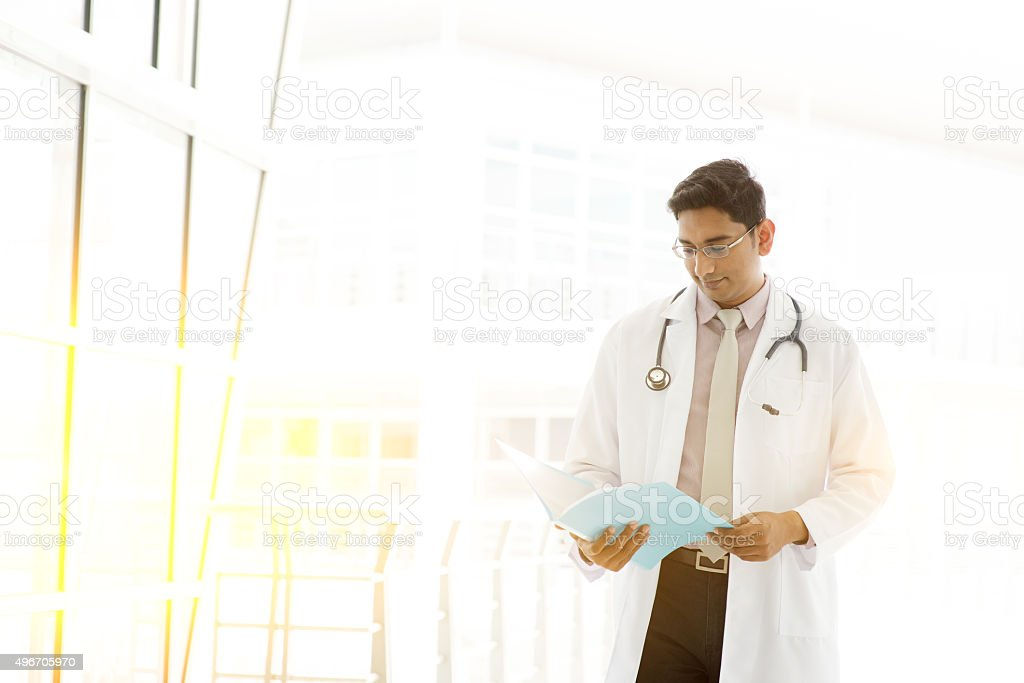 Asian Indian doctor reading medical report stock photo