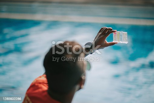 Asian indian lifeguard Pool testing kit being used in a swimming pool for water chlorine level