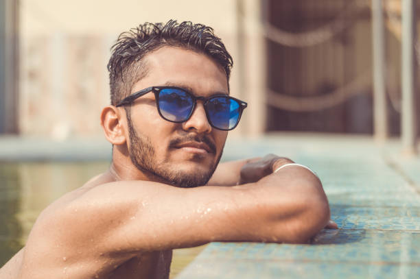 Asian Indian Male Relaxing By The Pool Stock Photo