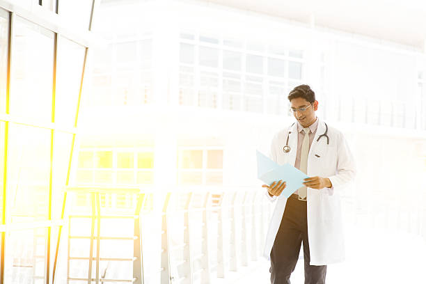 Asian Indian medical doctor walking at hospital corridor stock photo