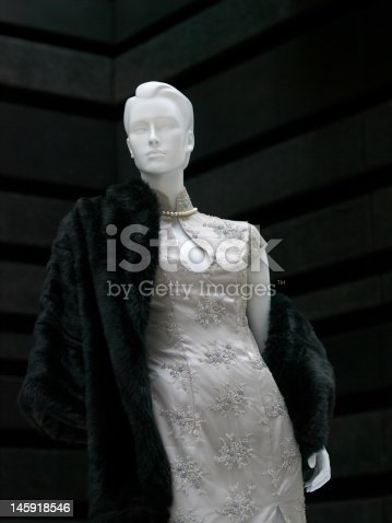 Mannequin dressed in an Asian inspired cheongsam styled evening dress with a pearl necklace, and draped with a rich, luxuriant, black fur coat, against a background textured with linear patterns