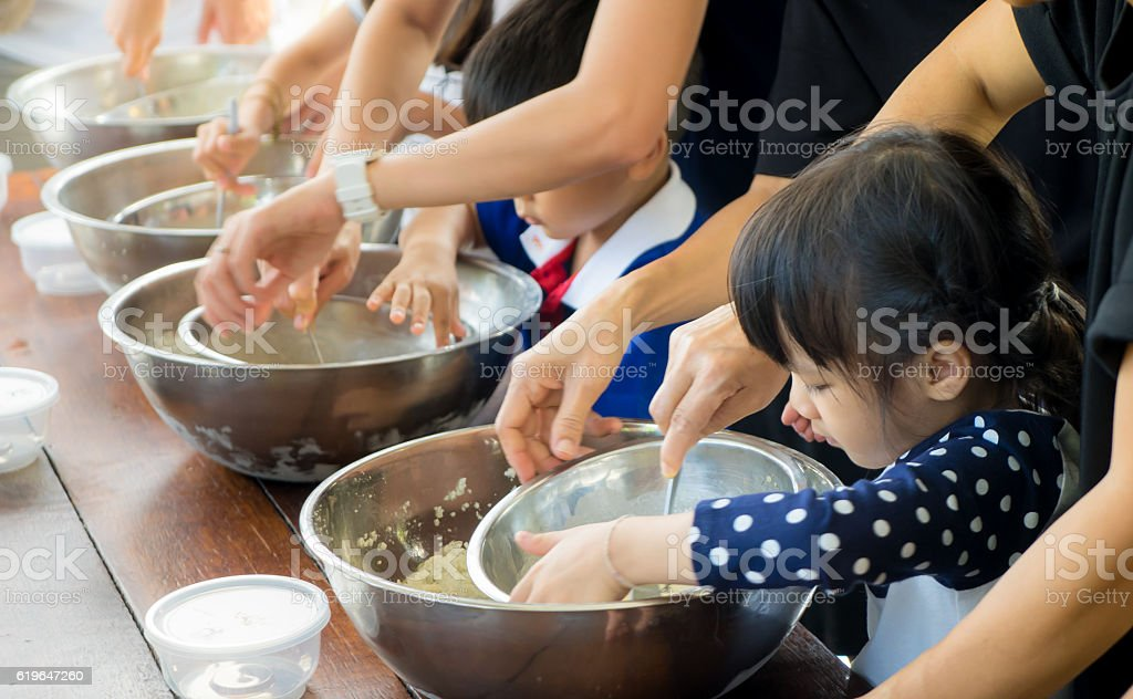Asian kid and family is making ice cream in class. stock photo