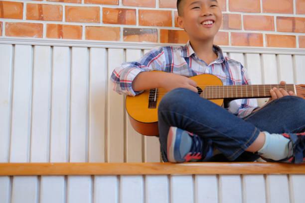 asiatische junge junge Kind Gitarre Ukulele zu spielen. Kinder-Freizeit-Aktivität – Foto